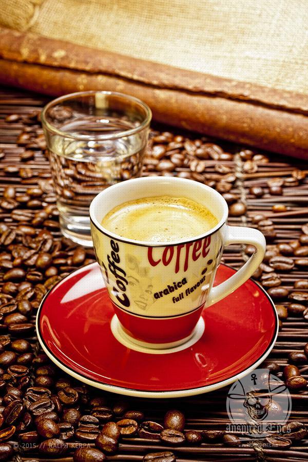 Eine Tasse Espresso mit einem Wasserglas und Kaffeebohnen // Foto: Ralph Kerpa