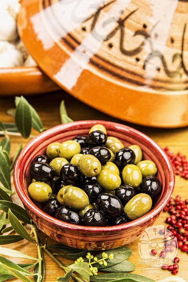 Grüne und schwarze Oliven in einer Schale mit Olivenzweigen, Pfeffer und Knoblauch // Foto: Ralph Kerpa