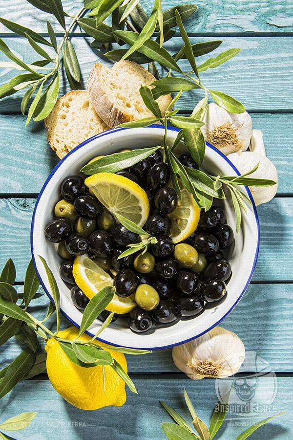Grüne und schwarze Oliven in einer Schüssel mit Olivenzweigen, Brot und Zitrone // Foto: Ralph Kerpa