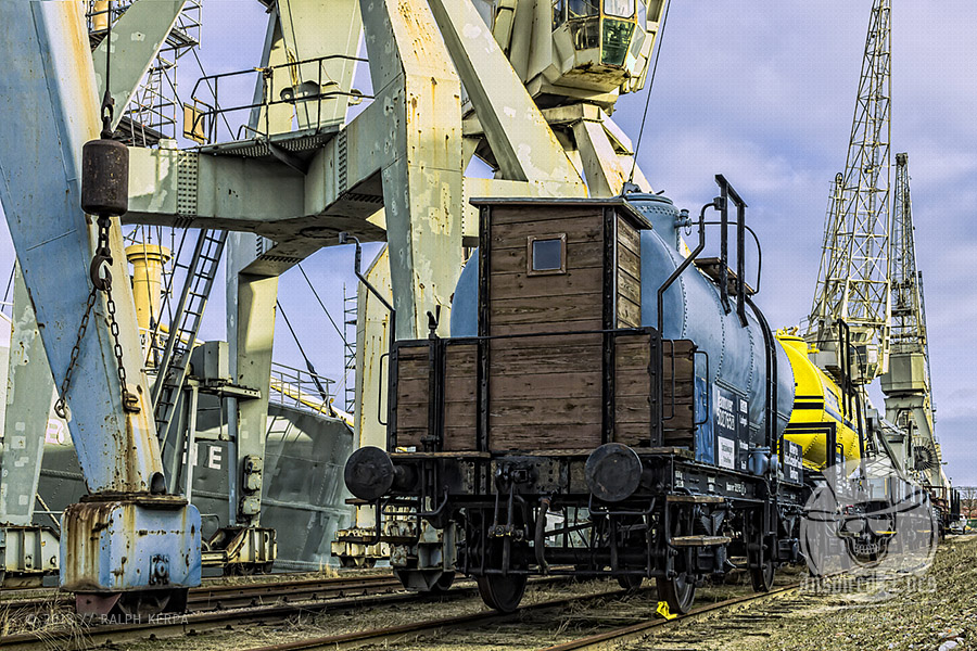 """Alte Kesselwagen vor Ladekranen an einer Kaimauer, mit dem festgemachten Stückgutfrachter """"MS Bleichen"""" im Hamburger Museumshafen // Foto: Ralph Kerpa"""