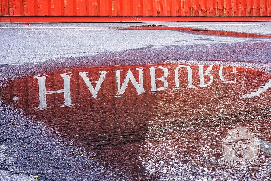 Die Aufschrift von einem Container spiegelt sich in einer Pfütze // Foto: Ralph Kerpa