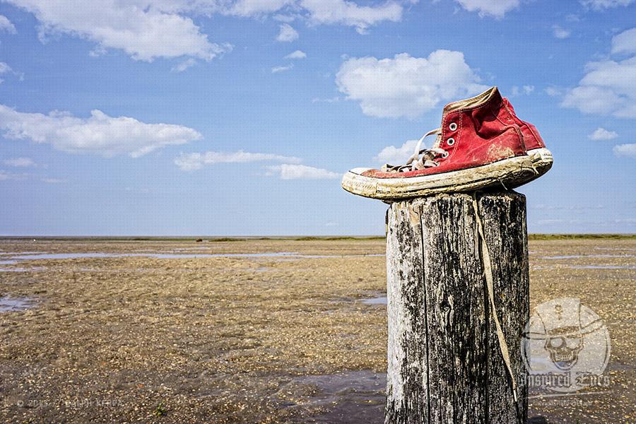 Zurückgelassene Sneaker auf einem Holzpfahl am Strand // Foto: Ralph Kerpa
