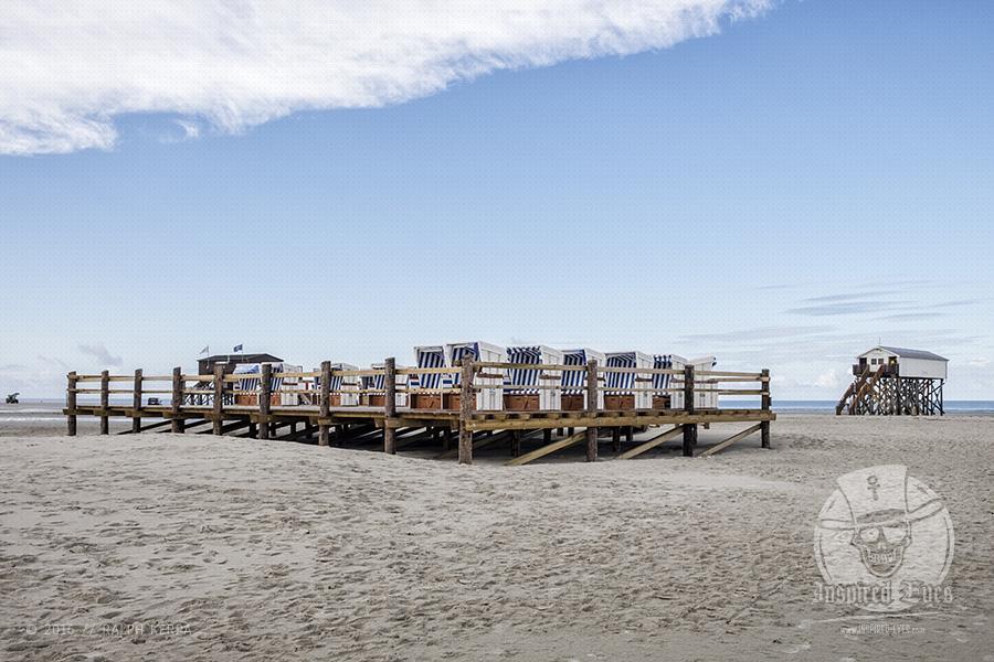 Eine Plattform mit Strandkörben am weitläufigen Strand von St. Peter-Ording